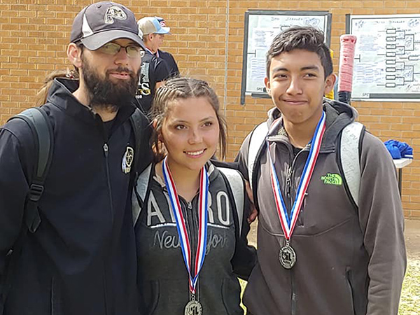 Tennis Coach Jeff Braziel and state qualifying mixed doubles team of seniors Alyssah Herrera and Camren Flores with their medals following the regional torunament