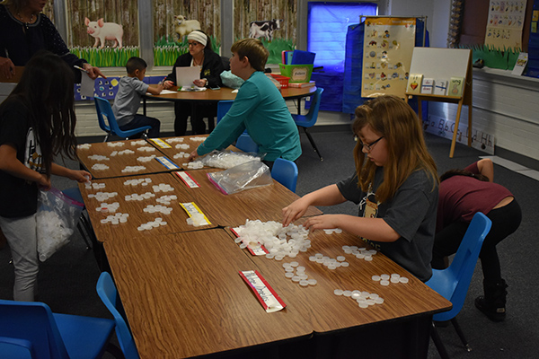 Classes work to count the bottle caps collecting during the contest.