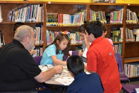 Students look through a pile of stamps with Mr. Hill at the stamp club meeting.