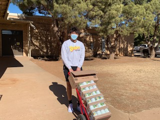 Senior Jayden Mendoza carts canned goods from the school out to deliver to Alcove Care for the 2020 Food Drive.