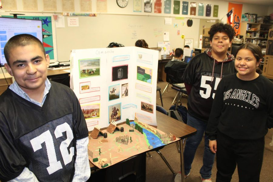 Seventh-graders Martin Franco, Bishop Keeling and team leader Evolet Vigil with their presentation display on the Comanche tribe.